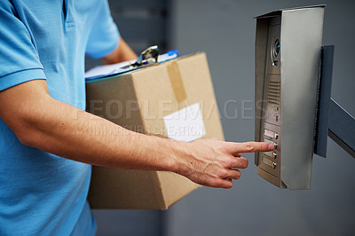 Buy stock photo Closeup shot of a courier ringing an intercom while making a delivery