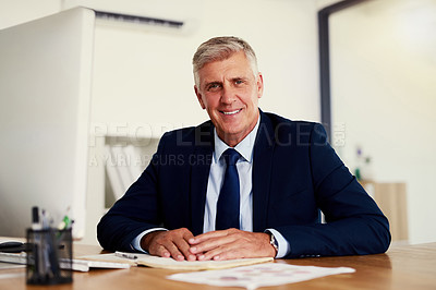 Buy stock photo Portrait of a confident mature businessman sitting at his desk in an office