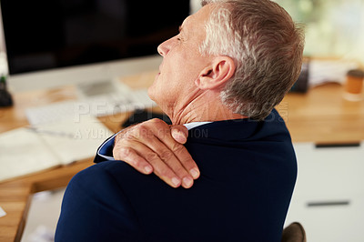 Buy stock photo Cropped shot of a mature businessman experiencing shoulder pain while working in an office