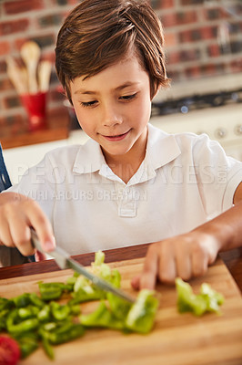 Buy stock photo Shot of an adorable little boy chopping vegetables on his own in the kitchen
