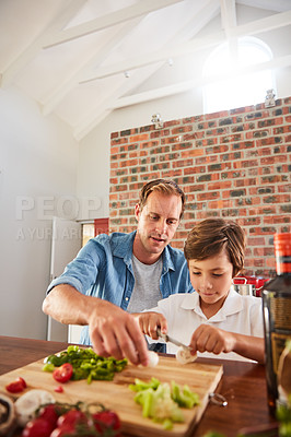 Buy stock photo Shot of a father watching his little boy chop vegetables in the kitchen