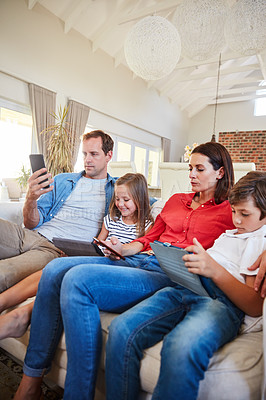 Buy stock photo Shot of a young family sitting together on their living room sofa distracted by various media and devices