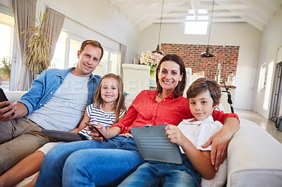 Buy stock photo Portrait of a smiling family sitting together on their living room sofa using various media and devices