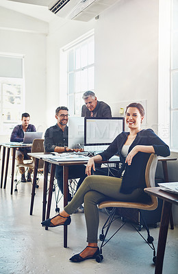 Buy stock photo Portrait of young businesswoman using a computer at work with her colleagues in the background