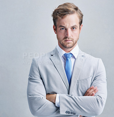 Buy stock photo Studio shot of a businessman in a grey suit posing against a grey background