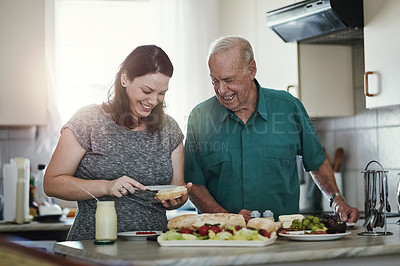 Buy stock photo Shot of a woman making her senior parent a sandwich