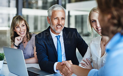 Buy stock photo Shot of businessmen shaking hands during a meeting at work