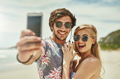 Buy stock photo Shot of an affectionate young couple taking selfies after their engagement on the beach