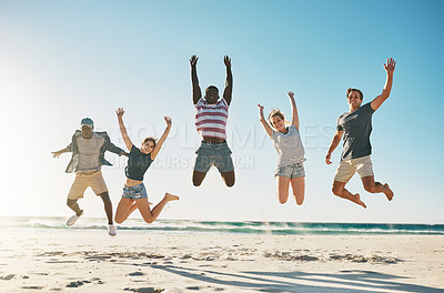 Buy stock photo Shot of a group of young friends jumping enthusiastically in the air at the beach