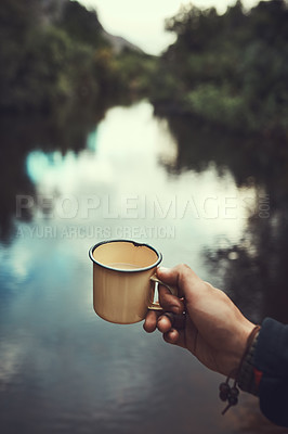 Buy stock photo Cropped shot of an unidentifiable man holding a mug with the river in the background