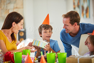 Buy stock photo Shot of a little boy opening his birthday presents surrounded by his family