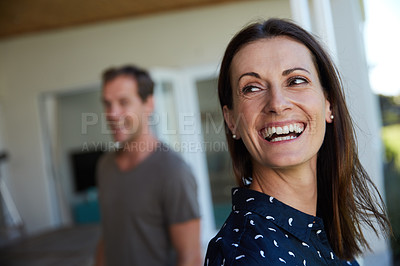 Buy stock photo Shot of a woman laughing with her husband blurred in the background