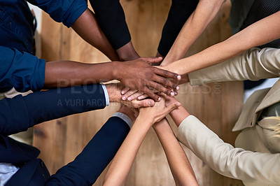 Buy stock photo High angle shot of a group of unidentifiable businesspeople piling their hands in unity in the office