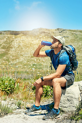 Buy stock photo Shot of a young man taking a break while out on a hike