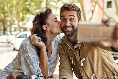 Buy stock photo Shot of a happy tourist couple taking a selfie while relaxing at a sidewalk cafe together