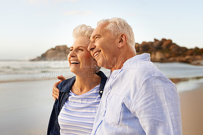 Buy stock photo Shot of a happy senior couple looking out towards the sea at the beach