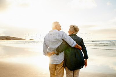 Buy stock photo Shot of a happy senior couple watching the sunset at the beach