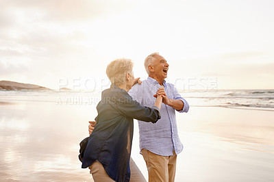 Buy stock photo Shot of a happy senior couple dancing at the beach
