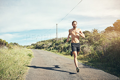 Buy stock photo Shot of a bare chested young man out for an early morning run