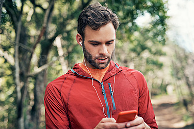 Buy stock photo Shot of a young man listening to music on an mp3 player while out for a run in the forest