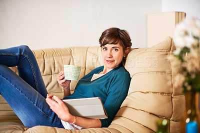 Buy stock photo Shot of an attractive young woman chilling on the sofa with her tablet