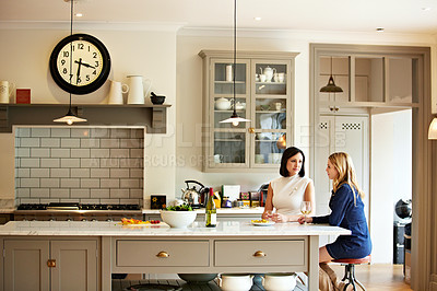 Buy stock photo Shot of two young woman having a chat while sitting in the kitchen