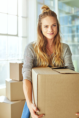 Buy stock photo Shot of a beautiful young woman carrying a box while moving house