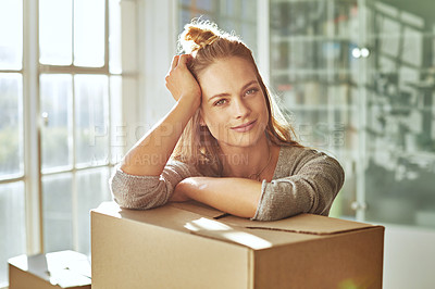 Buy stock photo Shot of a beautiful young woman leaning on a box while moving house