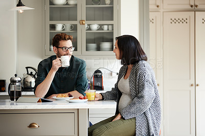 Buy stock photo Shot of a young man having breakfast with his pregnant wife in the kitchen