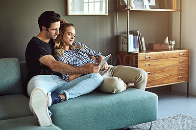 Buy stock photo Shot of an affectionate young couple using a tablet while sitting on a sofa at home