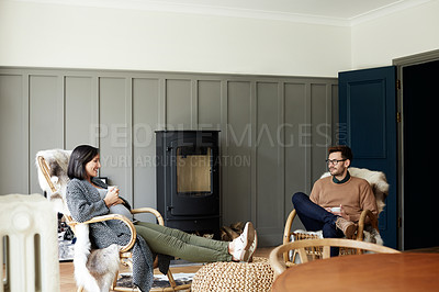 Buy stock photo Shot of a young man and his pregnant wife relaxing in their  living room