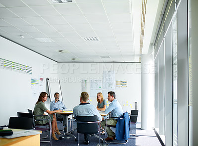 Buy stock photo Shot of a group of professional businesspeople meeting in the boardroom