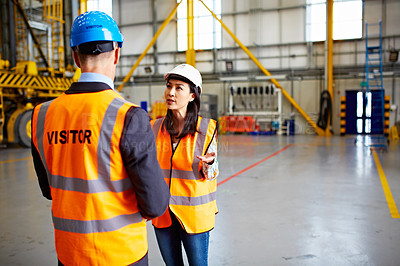 Buy stock photo Shot of two dock workers talking together inside of a large warehouse