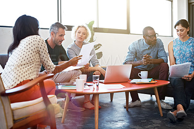 Buy stock photo Shot of a group of businesspeople looking over some paperwork in the office