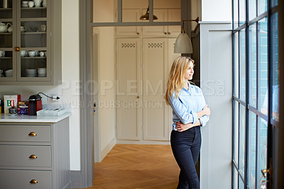 Buy stock photo Shot of a young woman looking out the window at home