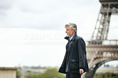 Buy stock photo Shot of a handsome mature man walking with his suitcase in front of the Eiffel Tower