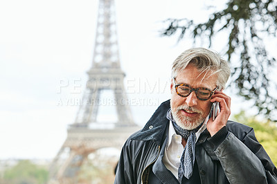 Buy stock photo Shot of a handsome mature man talking on a cellphone in Paris with the Eiffel Tower in the background