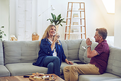 Buy stock photo Shot of an affectionate mature couple having cheese and wine on the sofa at home