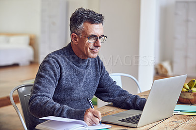 Buy stock photo Shot of a handsome and mature businessman working from home