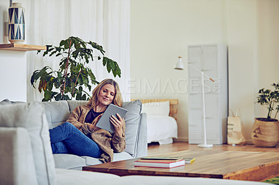 Buy stock photo Shot of a mature woman using her tablet while relaxing on the sofa at home