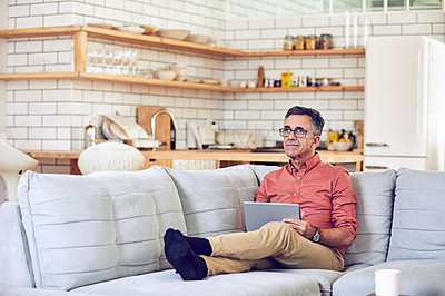 Buy stock photo Shot of a handsome and mature man using a tablet while relaxing on the sofa