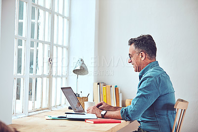 Buy stock photo Shot of a handsome and mature man working on his laptop at home
