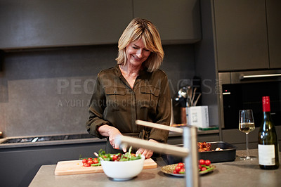 Buy stock photo Shot of a mature woman enjoying a glass of wine while preparing dinner in the kitchen