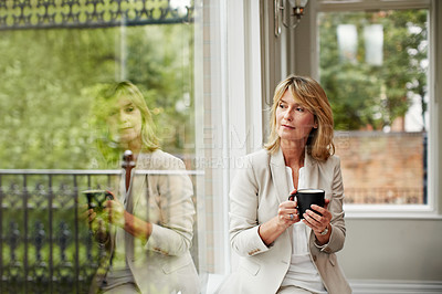 Buy stock photo Shot of a mature businesswoman sending a text message while sitting next to a window in her home