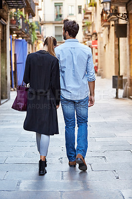 Buy stock photo Rearview shot of an affectionate young couple walking arm in arm together in the city
