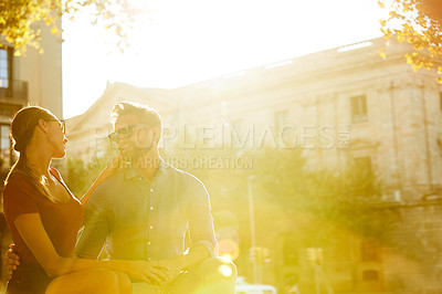 Buy stock photo Shot of a affectionate young couple sitting on a rooftop together at sunset