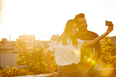Buy stock photo Shot of an affectionate couple taking a selfie while sitting on a balcony overlooking the city at sunset
