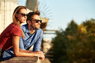 Buy stock photo Shot of a smiling young couple talking together while leaning on a balcony in the city looking at the view