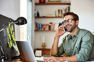 Buy stock photo Shot of a young man using he cellphone while sitting at a table and working from home