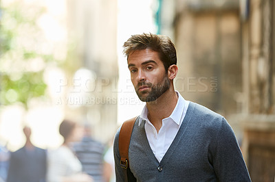Buy stock photo Cropped shot of a handsome and stylish young man walking through the city